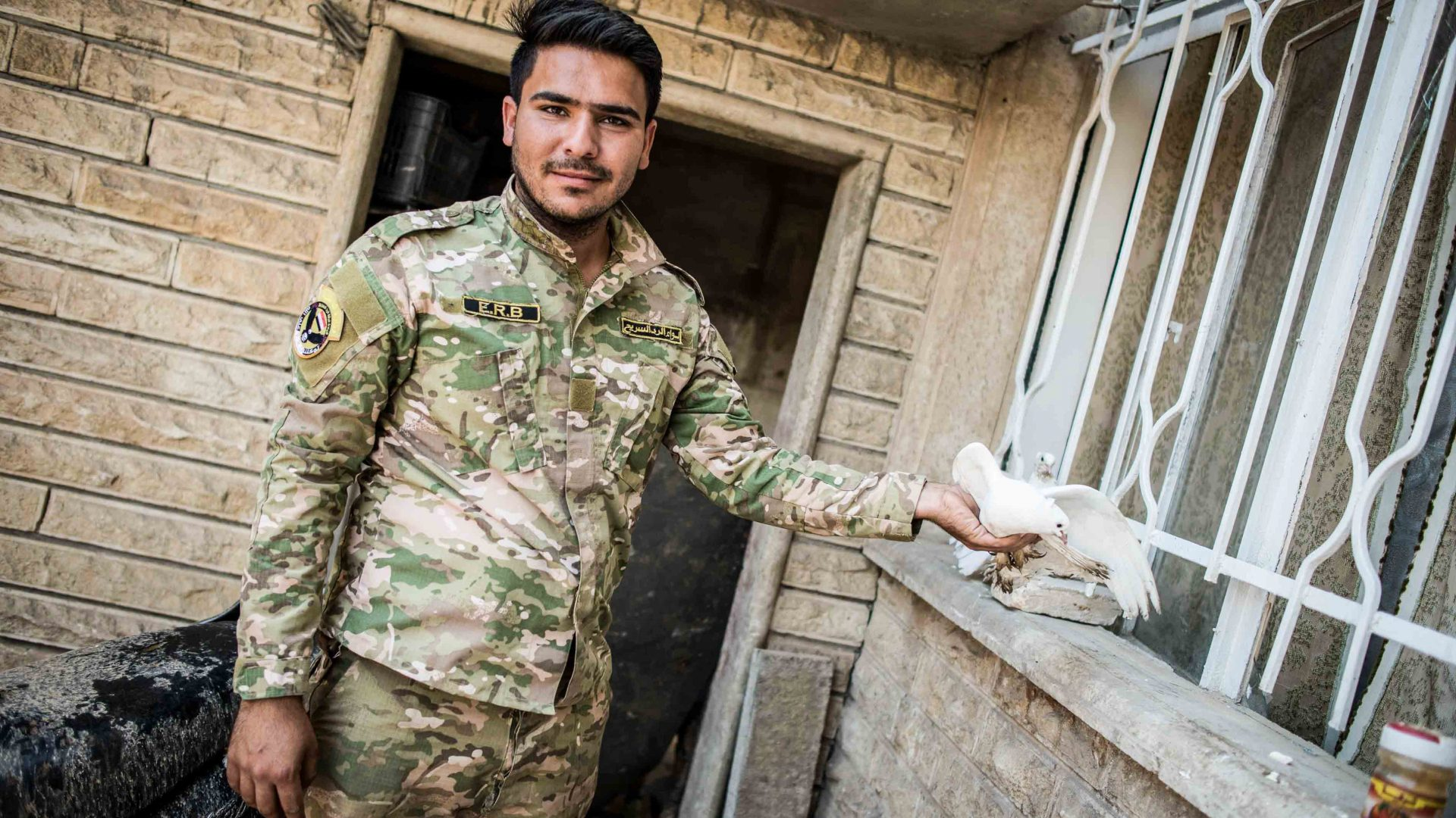 An Iraqi Emergency Response Division fighter poses with a dove in west Mosul.