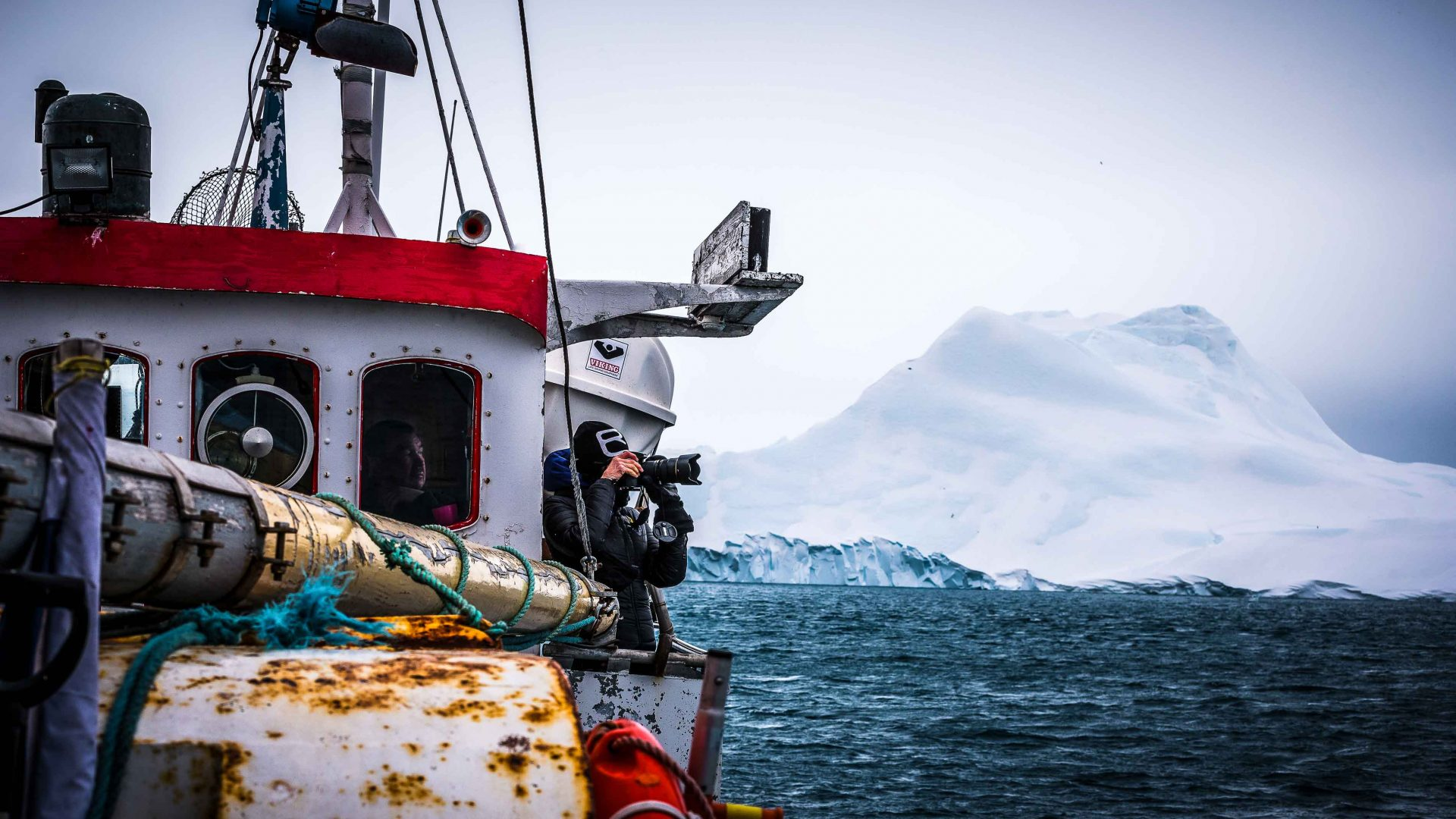 A photographer captures images of icebergs from the deck of a fishing boat as they float by in Ilulissat, Greenland.