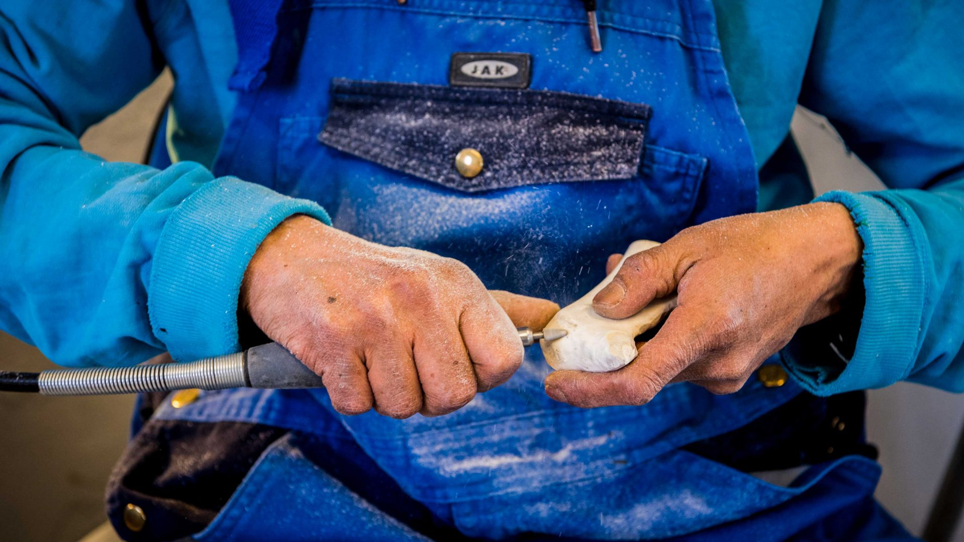 A local artisan carves a small keepsake sculpture out of whale bone in Ilulissat, Greenland.
