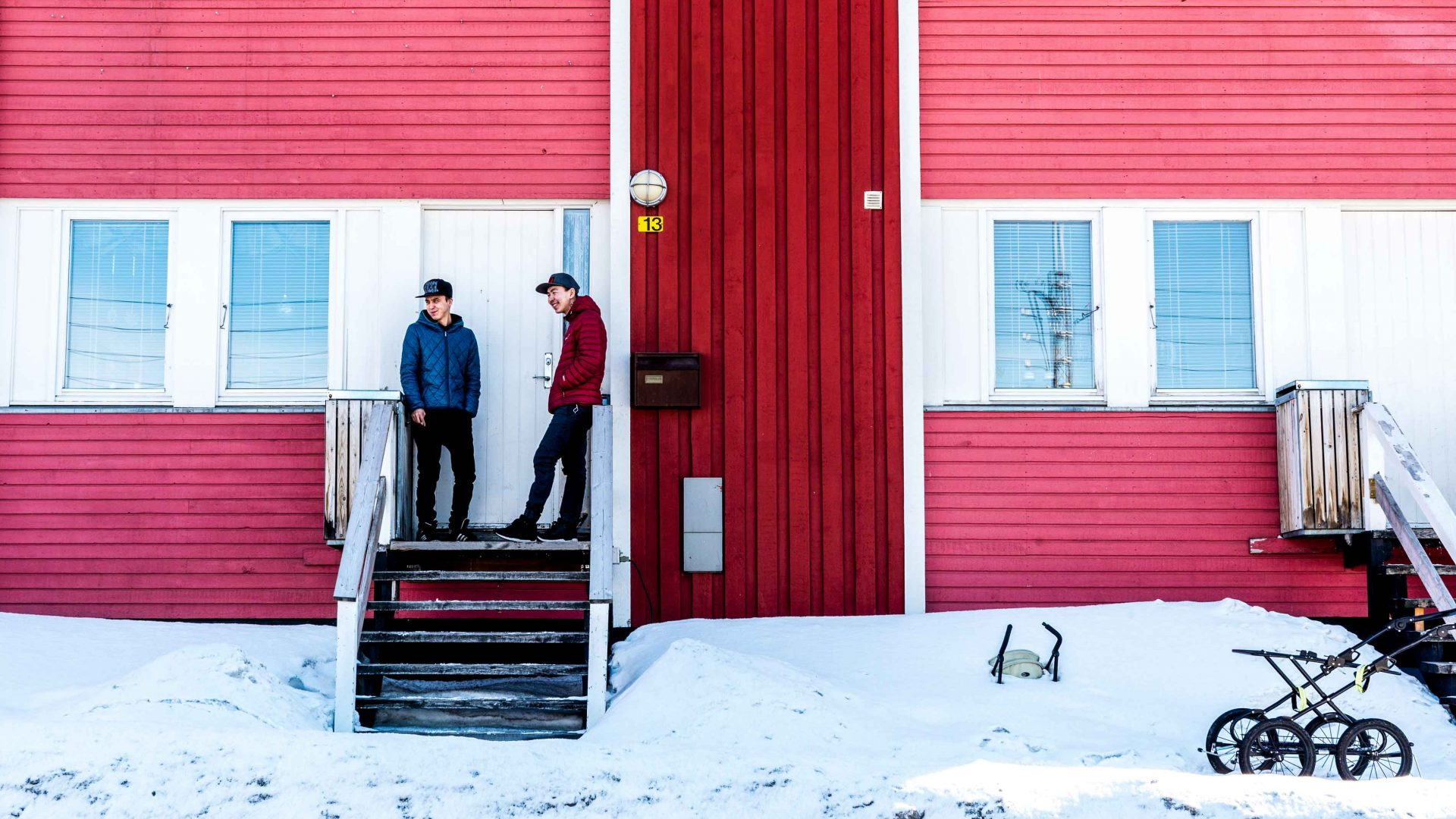 Inuit teenagers hanging out in front of one of Ilulissat's colorful apartment blocks.