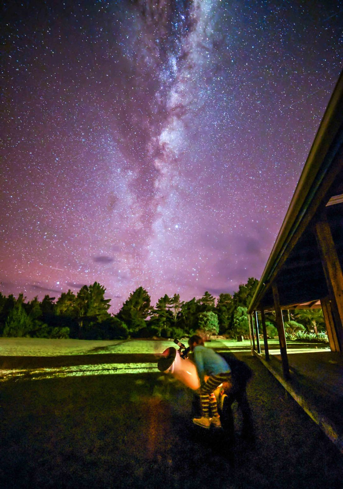 Stargazers view Great Barrier Island's night sky through a large telescope.