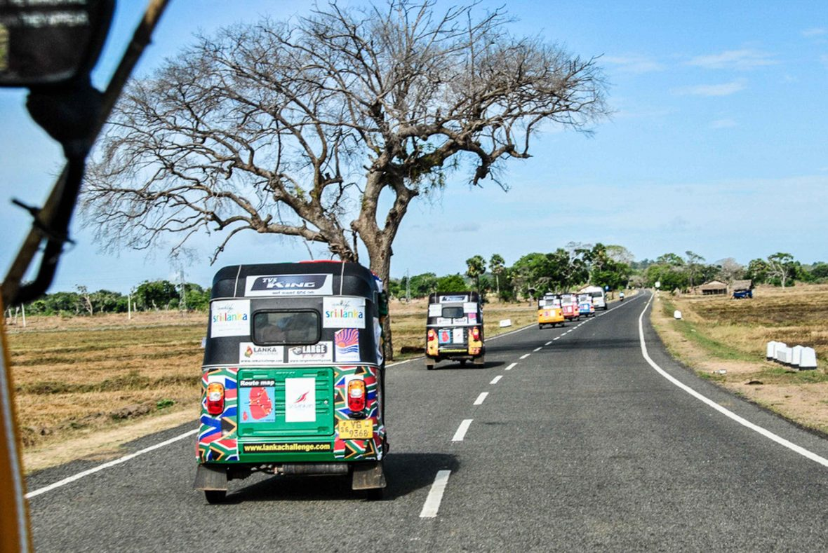 Tuk-tuks speed along an open road on the Lanka Challenge.
