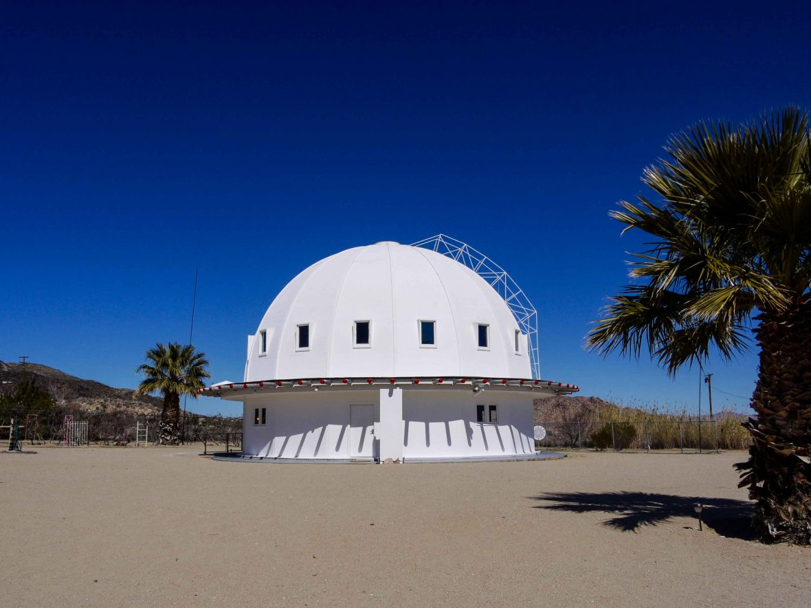 The Integratron's white walls stand in stark contrast to the rich blue sky of the desert where it lives.