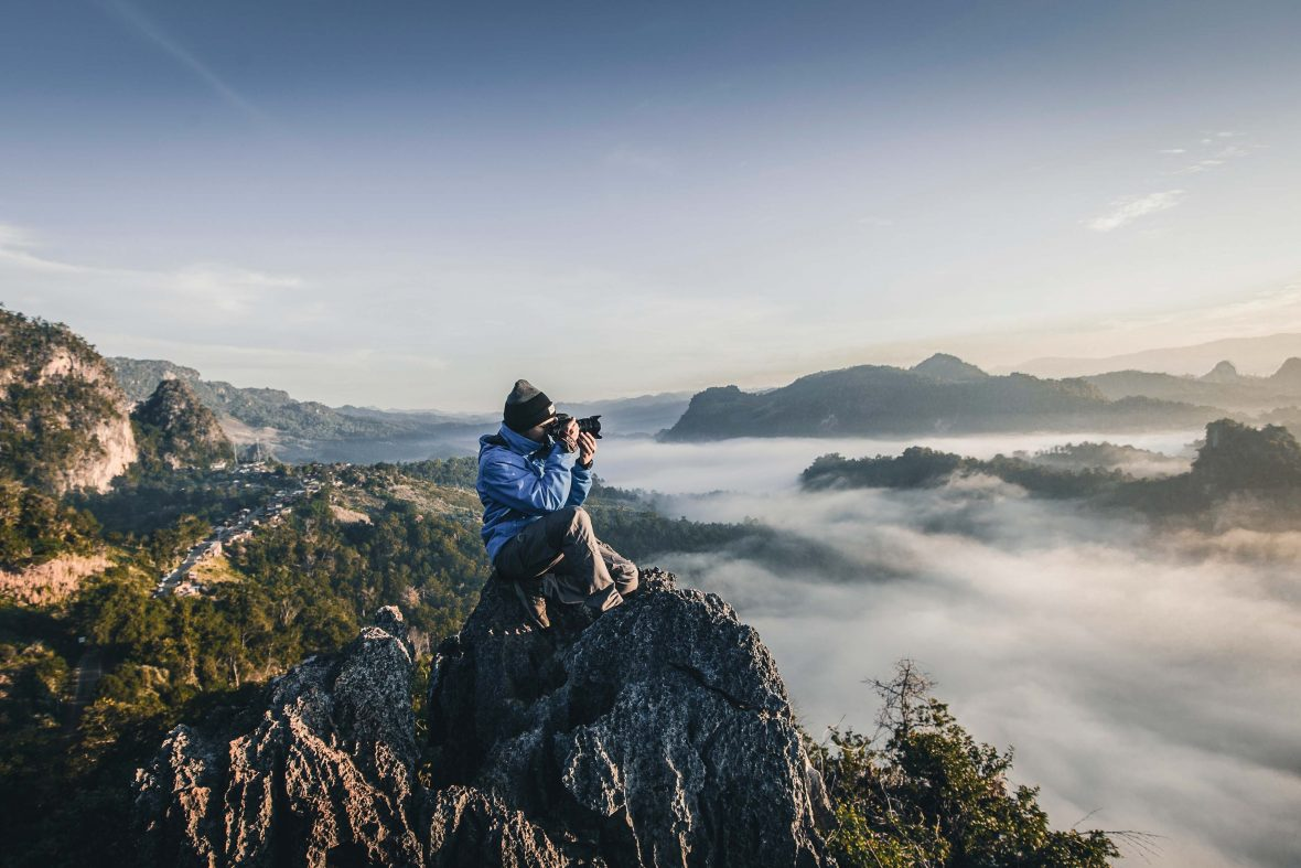 A woman takes a photo of a spectacular landscape.