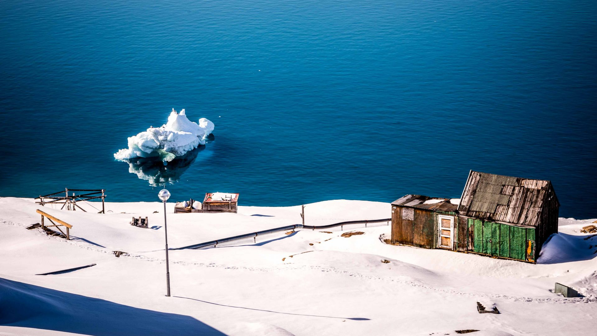 A green house sits by the water's edge in Ilulissat, Greenland
