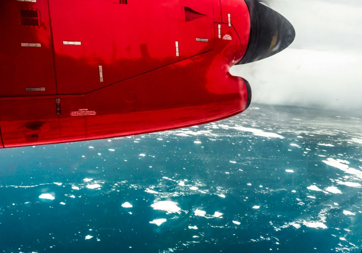 A red plane flies over the iceberg filled waters of Greenland.