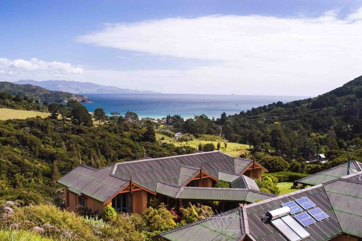 A solar-powered lodge in Great Barrier Island, New Zealand, sits overlooking the hills and ocean.