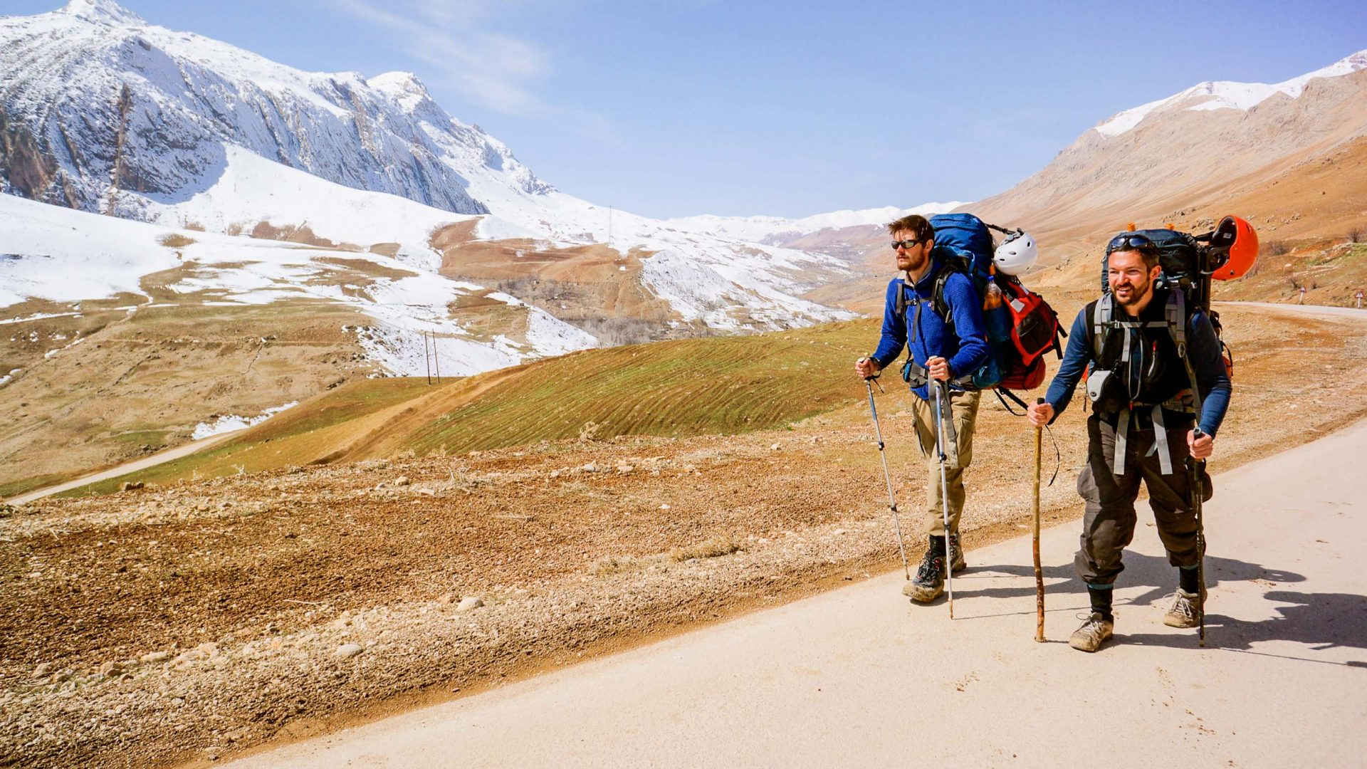 Leon McCarron and his travel companion Sean hike past melting snow fields along Karun River in Iran..