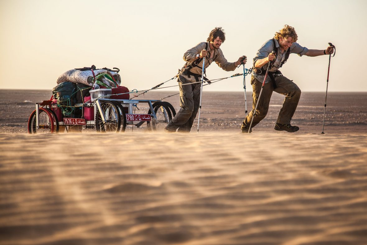 Leon McCarron and his travel companion pull their gear through the desert sands.