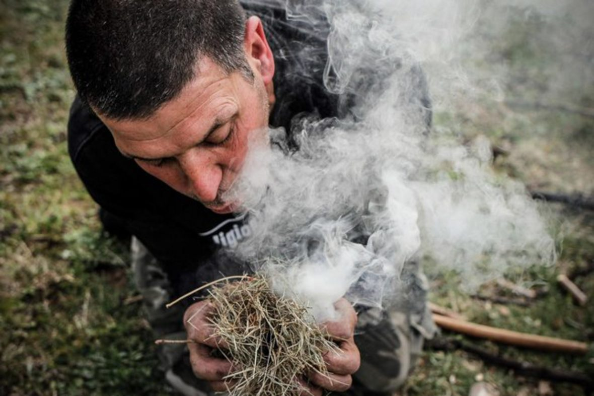 A Survival Course student learns how to make fire using a handmade bowline drill, tinder, a good old-fashioned elbow grease.