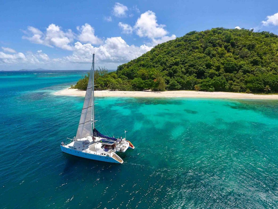 A boat sails through Dominica as one of the adventures you can do with Select Yachts.