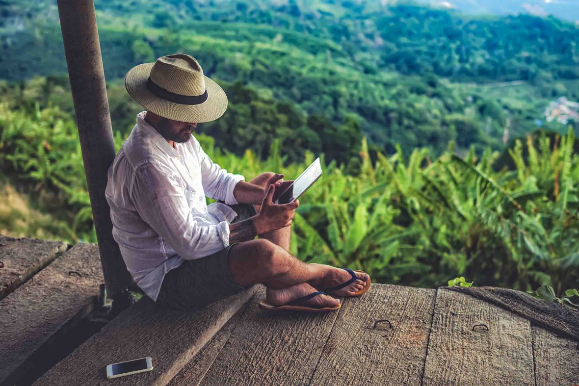 A traveler looks at his device while in nature.