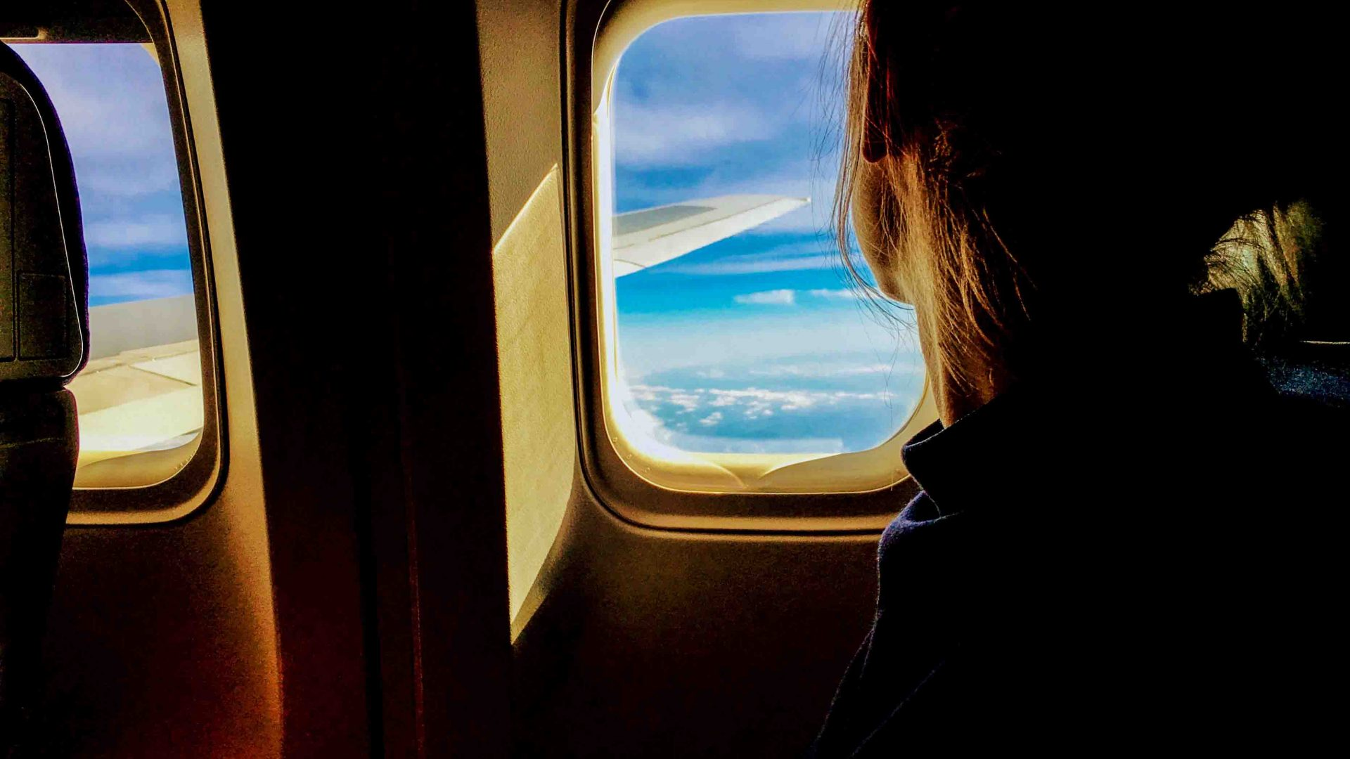 Fear of flying: A woman looks out the window of the airplane.
