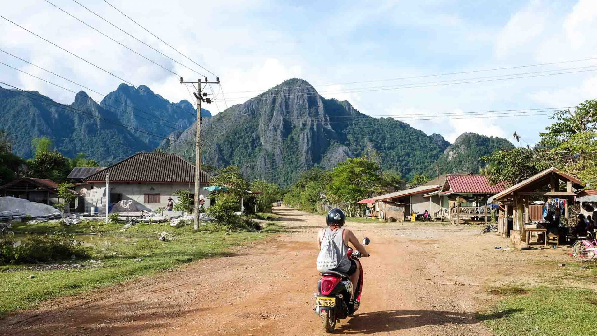 Riding through a rural Laos village on a scooter.