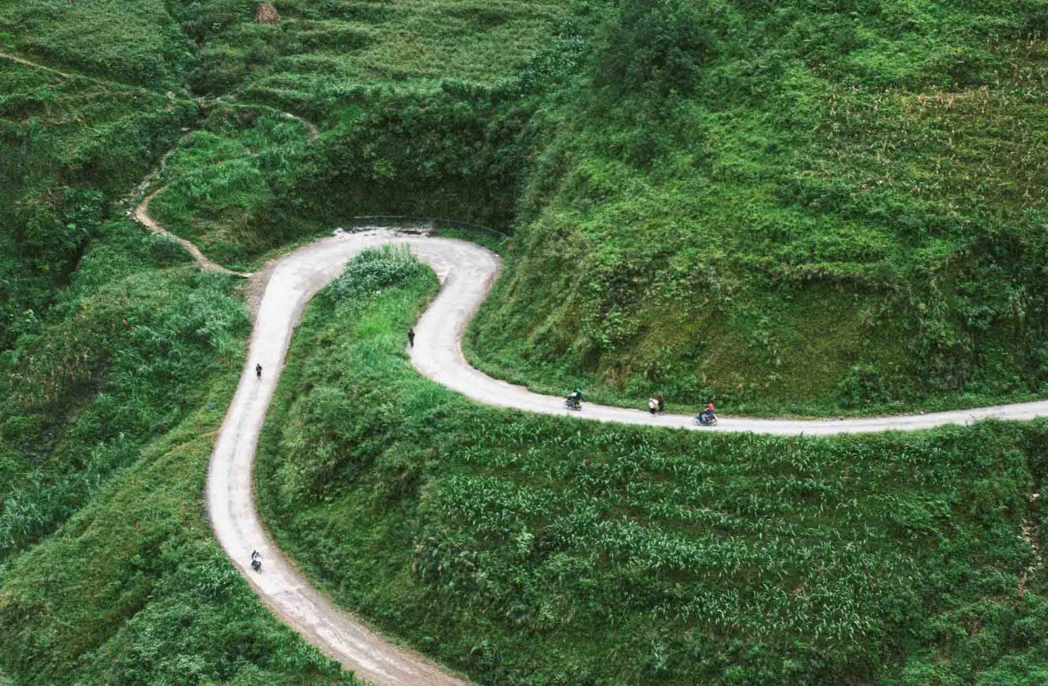People riding scooters can be seen riding down this winding road in Vietnam.