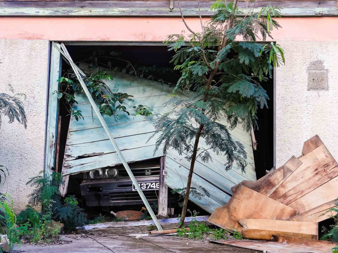An abandoned car in a collapsed garage in Montserrat.