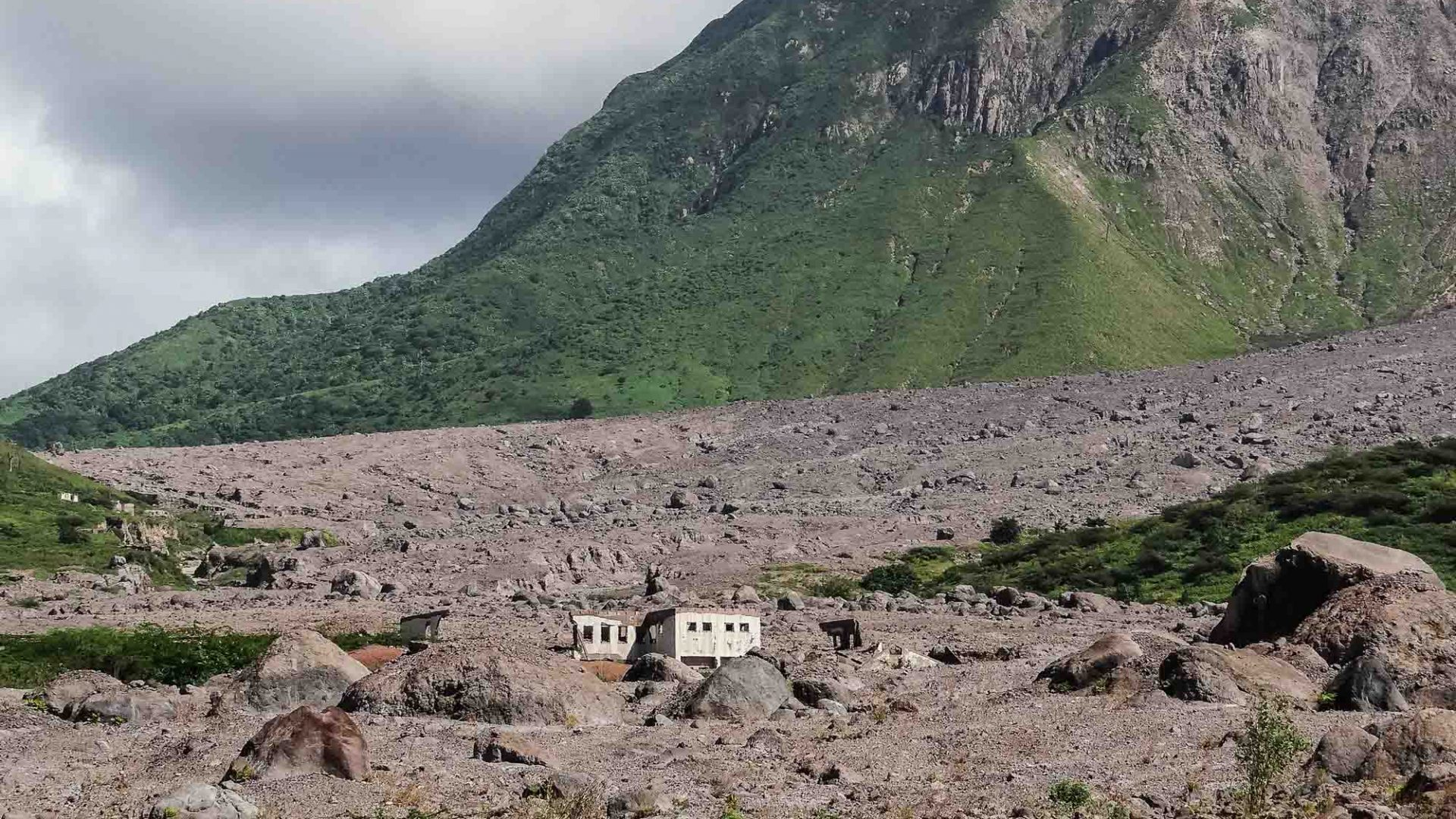 Montserrat's Soufrière Hills volcano stands behind an abandoned house in what has become known as a modern-day Pompeii.