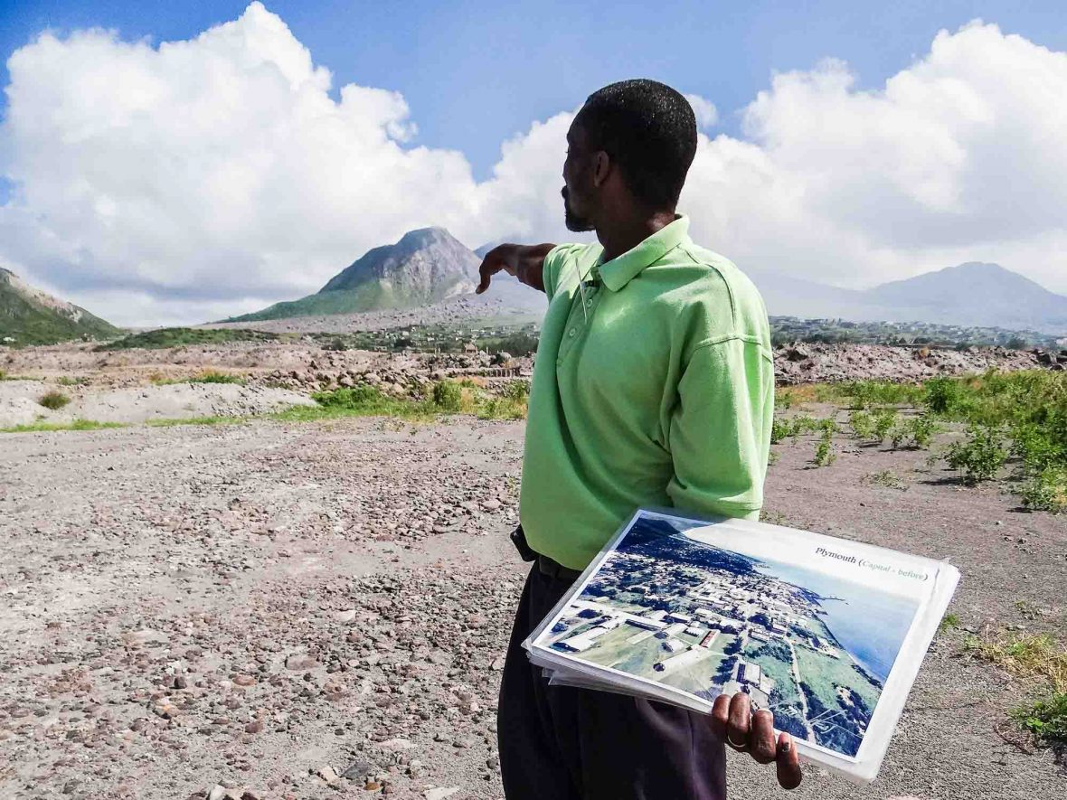 A tour guide points to where the city of Plymouth once stood in pre-eruption Montserrat.