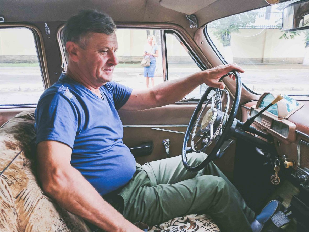 A driver in Transnistria shows off his 1960s vintage Soviet Volga car.