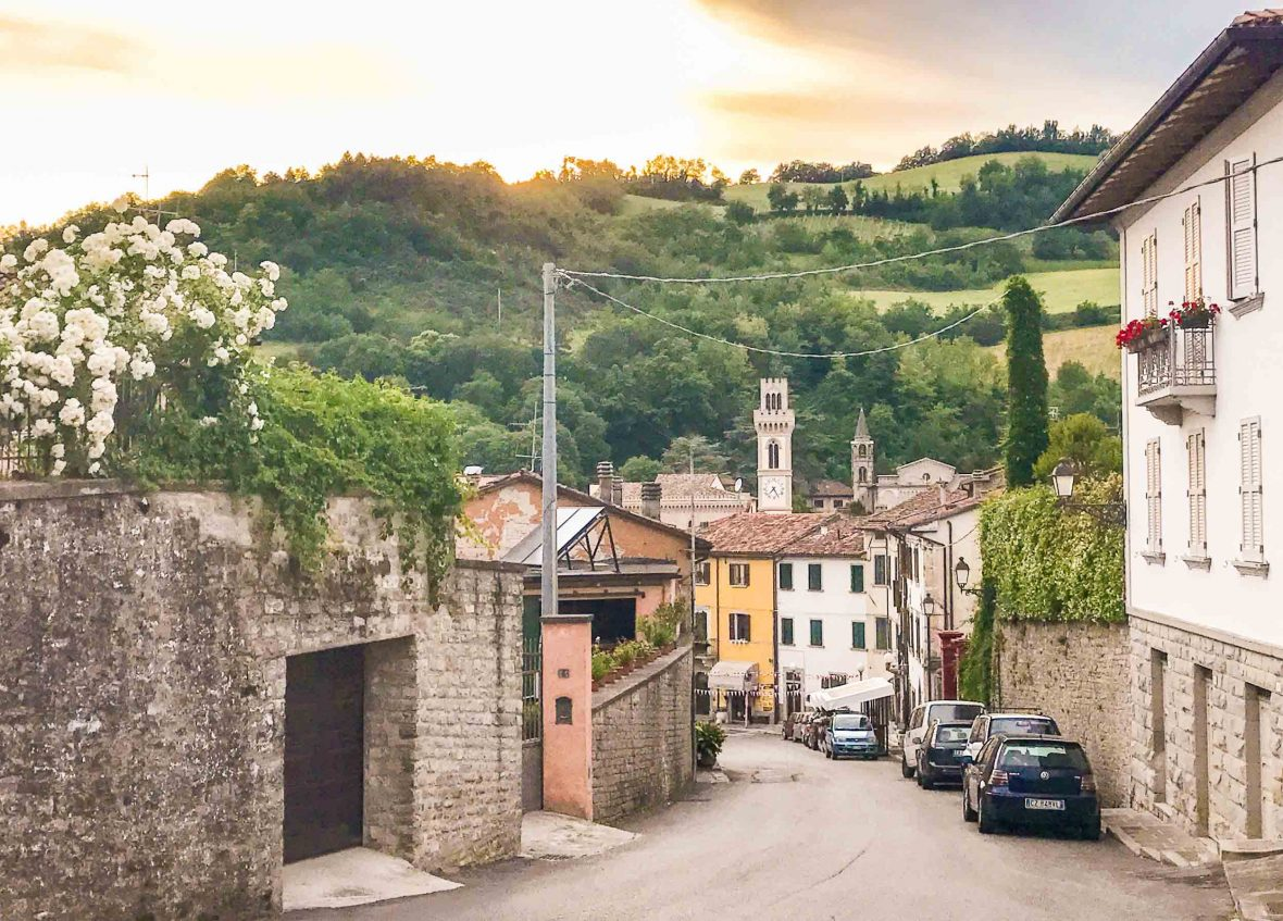 The winding roads lead past colorful houses to verdant green hills outside of Santa Sofia, Italy.