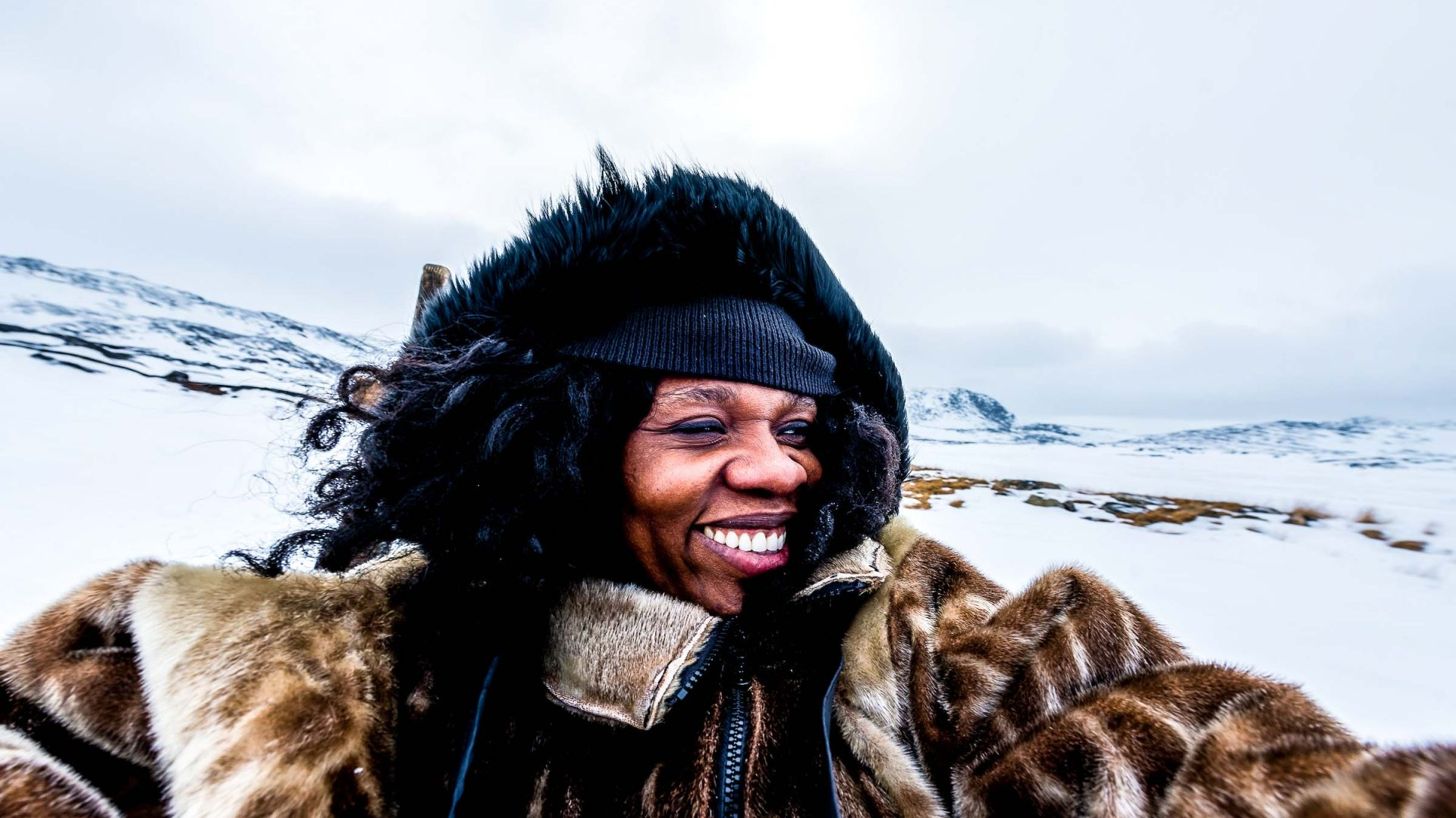 Adventure.com's featured contributor Lola Akinmade Åkerström, a Swedish-Nigerian travel photographer and author, during a dog sledding experience in Ilulissat, Greenland.