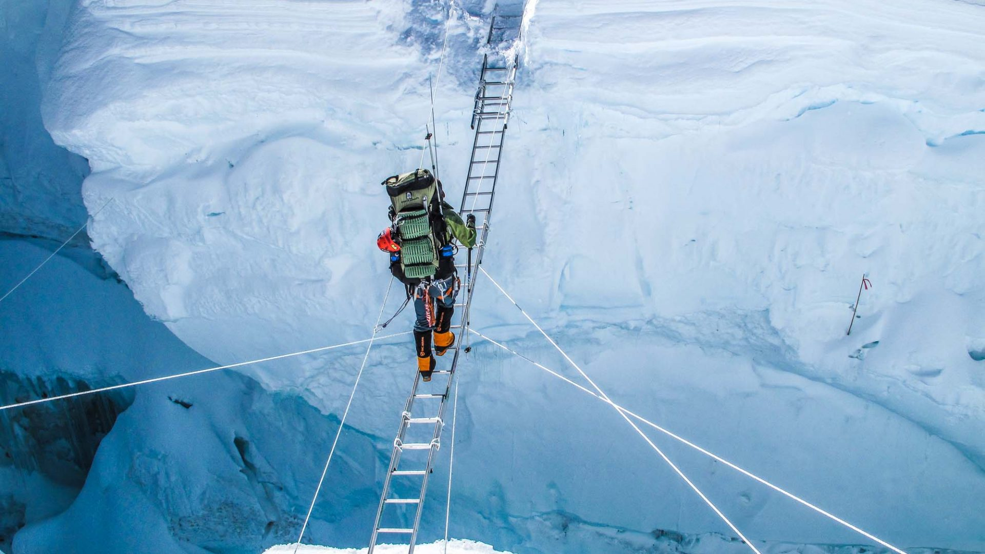Eric Larsen climbing over a crevasse on Mount Everest.