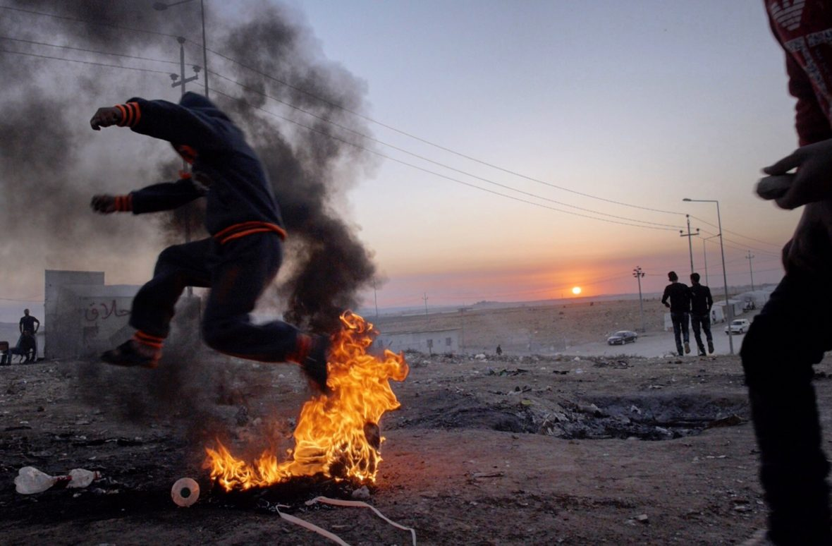 A boy jumps through a burning tyre fire in Dohuk, Iraqi Kurdistan.