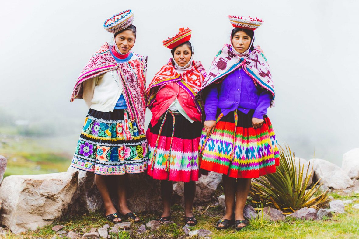Three Peruvian women from the Huacahuasi Valley near Machu Picchu in colorful traditional attire.