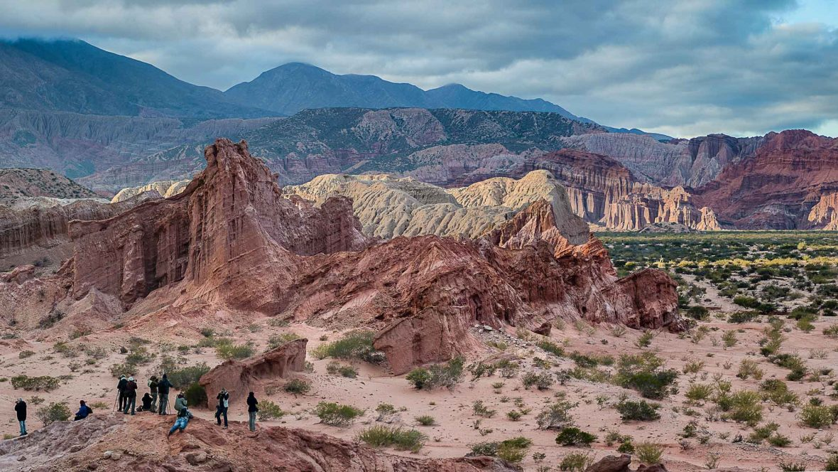 Photo: Sebastian del Val. Travelers look out at the vast rocky landscape in Salta, Argentina.