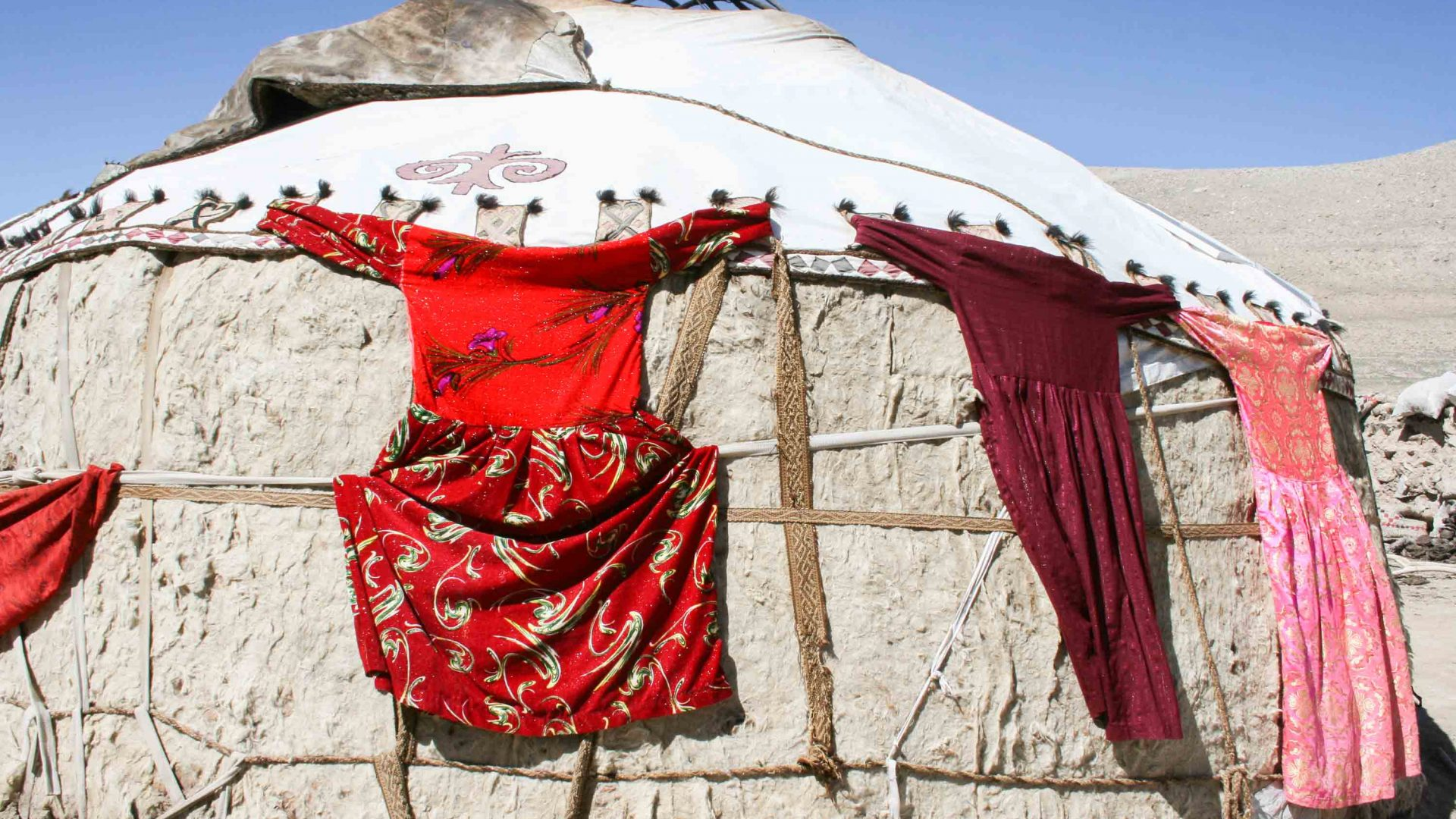 The brightly colored traditional clothes of the women from the Wakhan hang out to dry on the wall of a yurt.