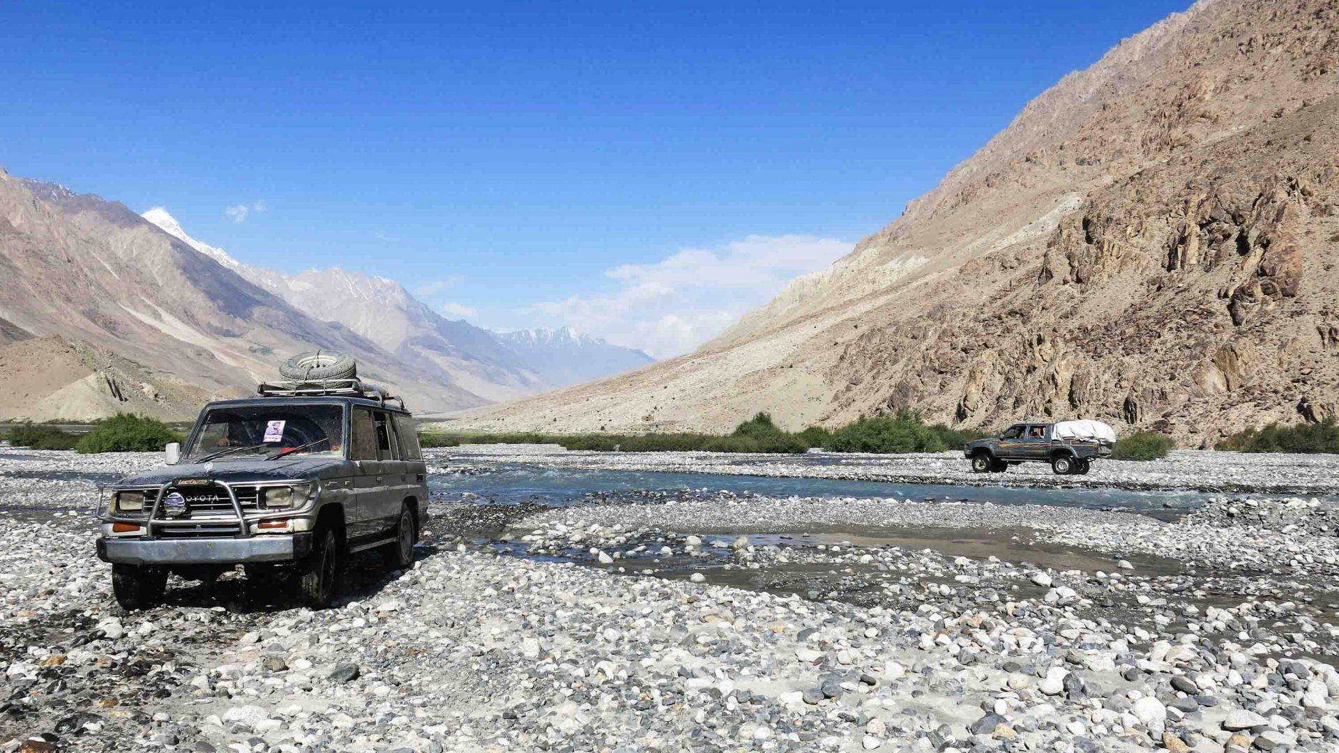 A tourist jeep drives through a river in the Wakhan, Afghanistan.