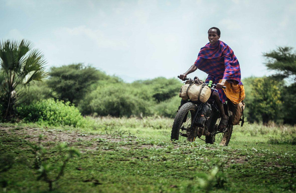 A Maasai man takes Ben's bike for a spin in Kenya.