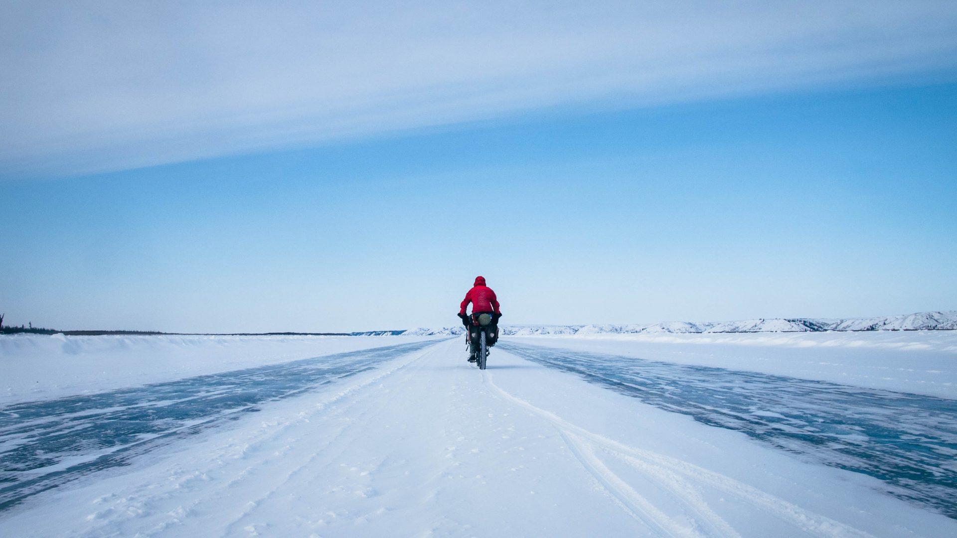 Cycling along the frozen MacKenzie River, Canada.