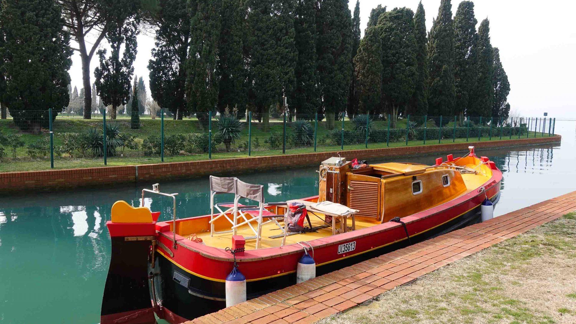 A traditional bragozzo boat moored at the monastery island of San Francesco del Deserto in Venice's lagoon.