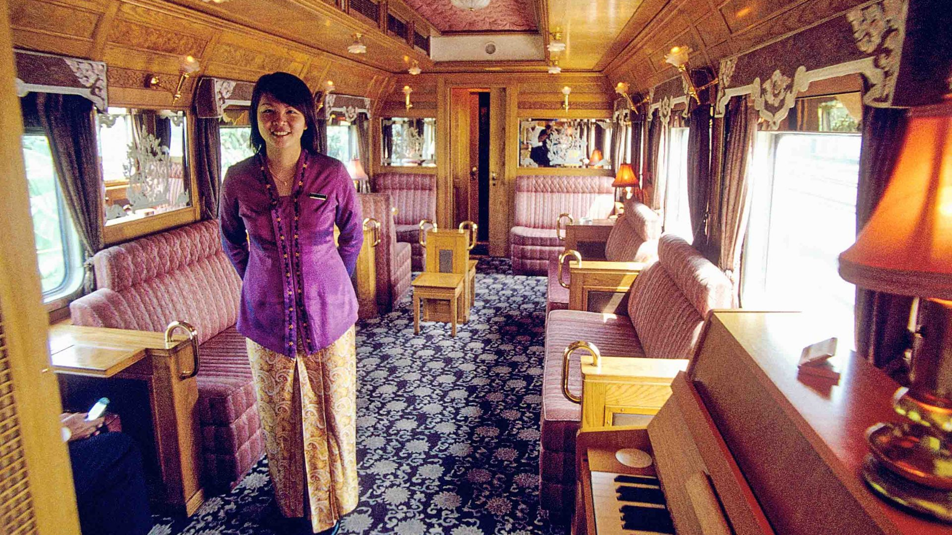 An employee smiles for the cameras on the luxurious Eastern and Oriental Express train in Thailand.