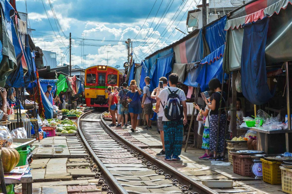 Tourists watch as the train rolls in at Maeklong market, Samut Songkhram, Thailand.