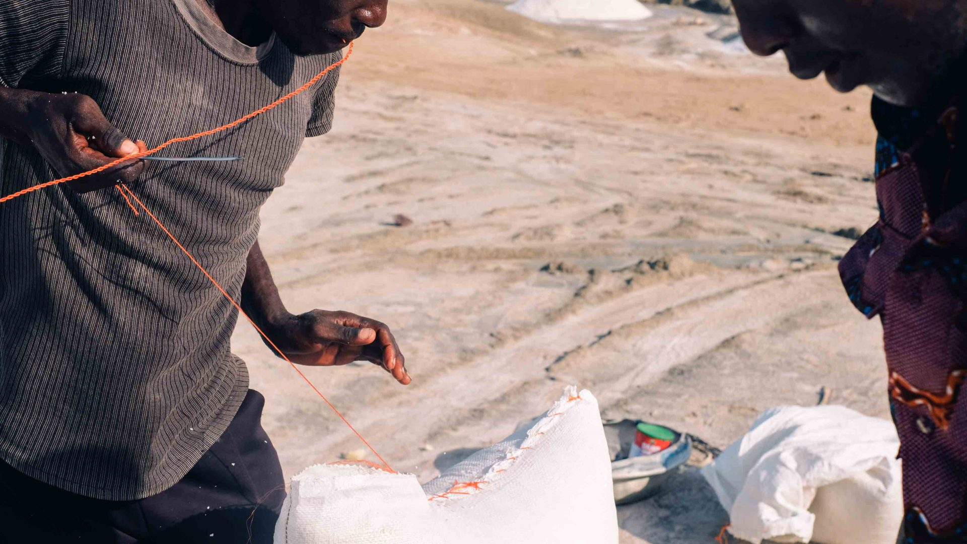 Two men working in the hot sun stitch up bags of salt with red string at Songor Salt Lagoon, Ghana.
