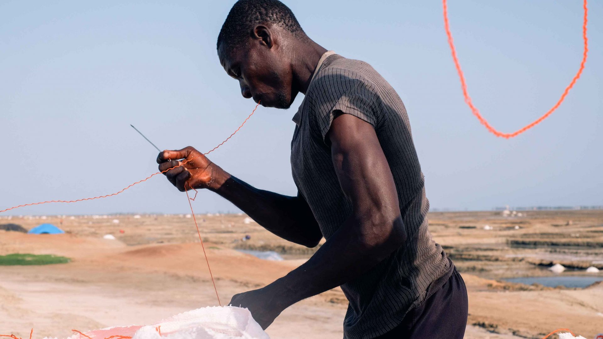 A man stitching up bags of salt with red string, Songor Salt Lagoon, Ghana.