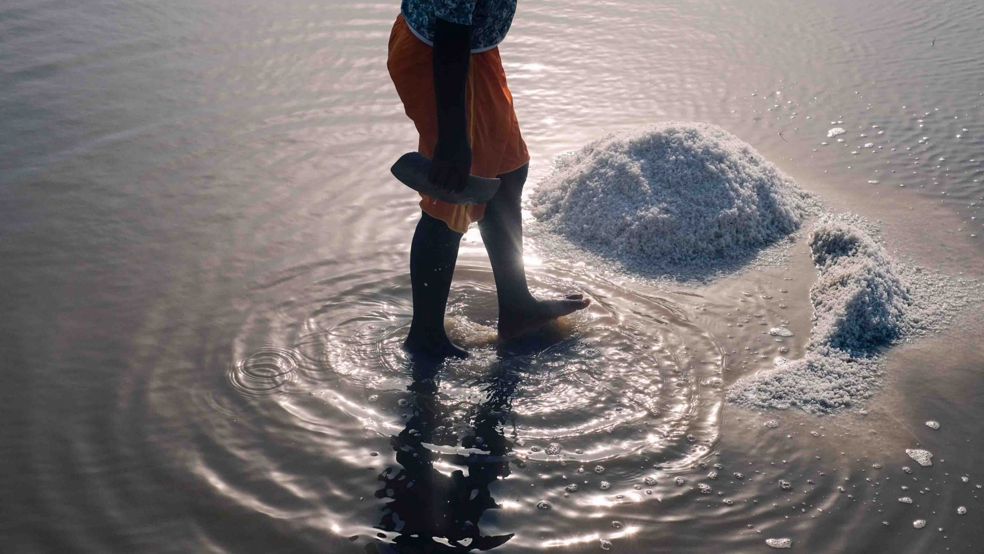 A woman standing in the middle of a salt field in Songor lagoon, Eastern Ghana.