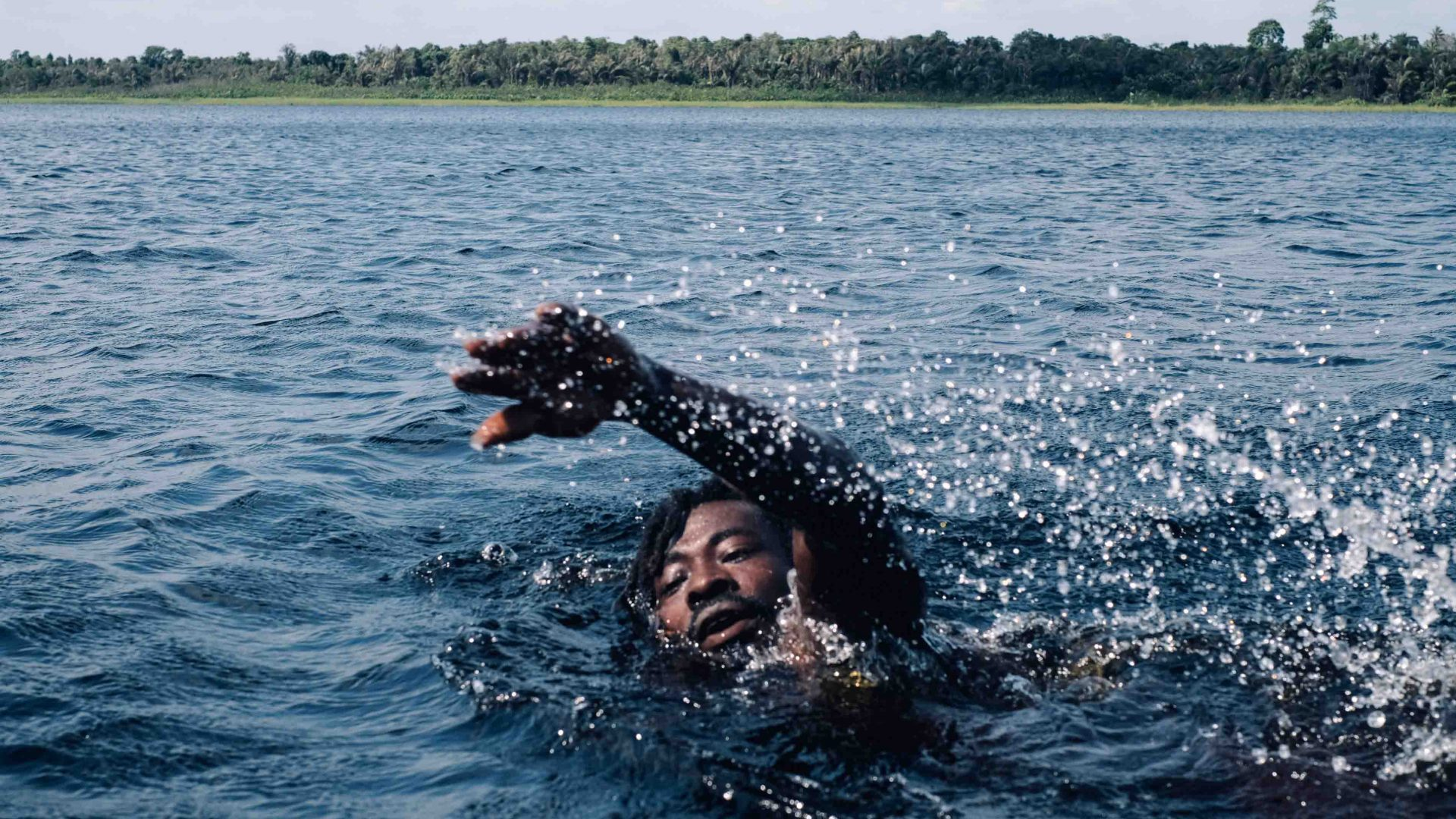 Jamaica, a local from the town of Beyin, cooling off in Nzulezu Lake, Western Region, Ghana.