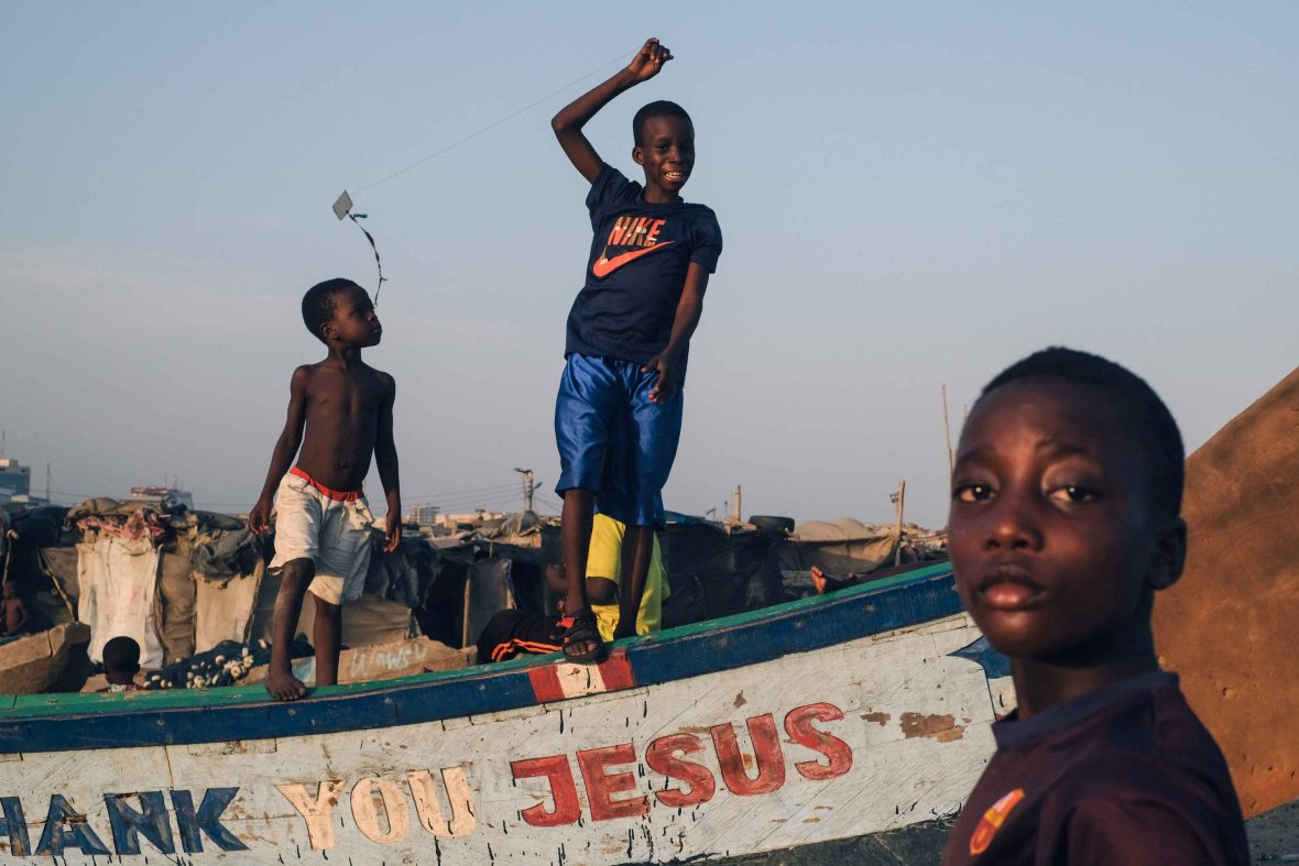 Local kids flying kites among the boats of the fishing neighborhood of Jamestown in Ghana's capital, Accra.
