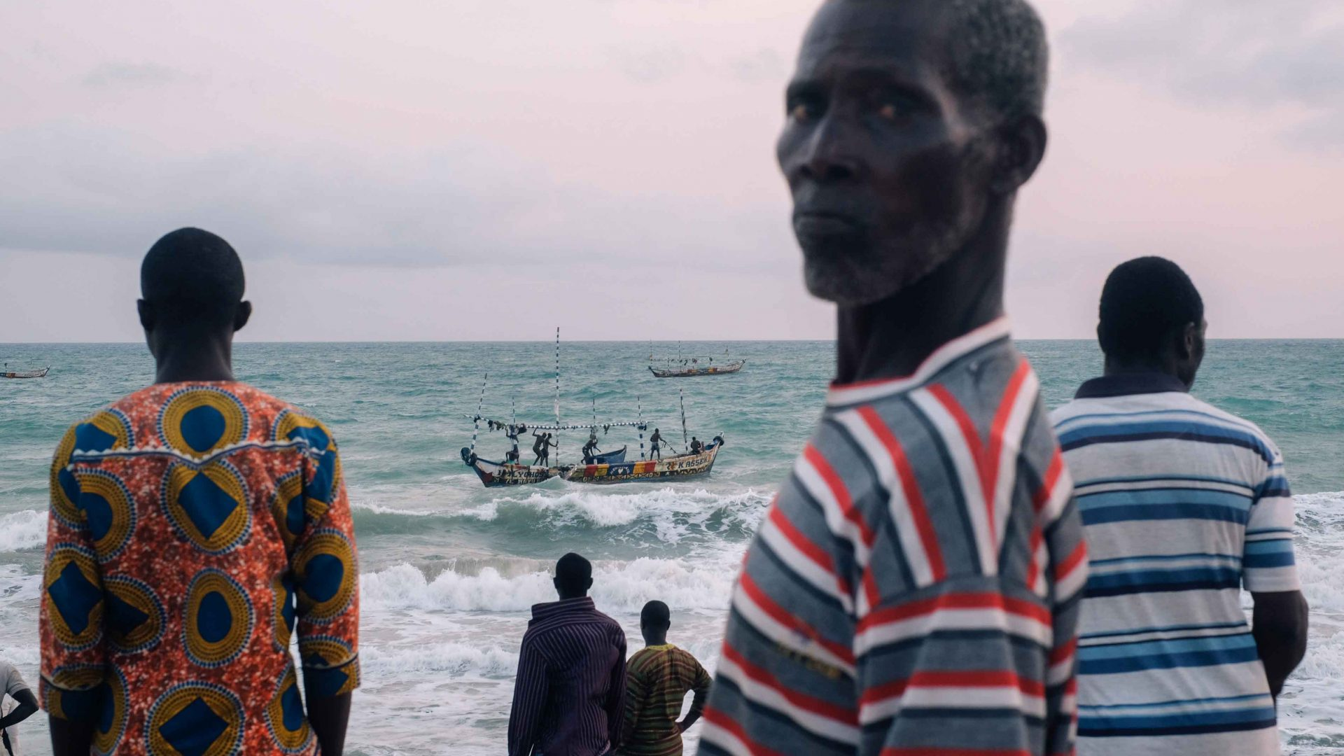 Fishermen wait for a boat to come in carrying the fish they have caught that day, Ada Foah, Volta Region, Ghana.