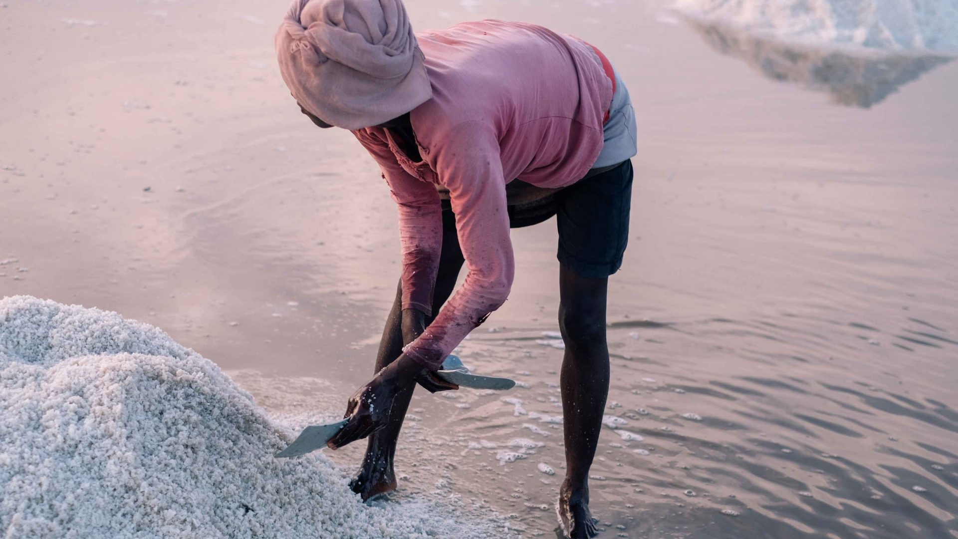 A woman harvests salt using traditional methods by hand at Songor Salt Lagoon in eastern Ghana.