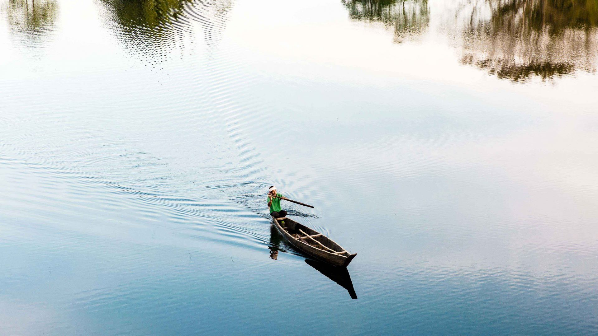 A man on a fishing boat in a small lake on Majuli Island, Assam, India.