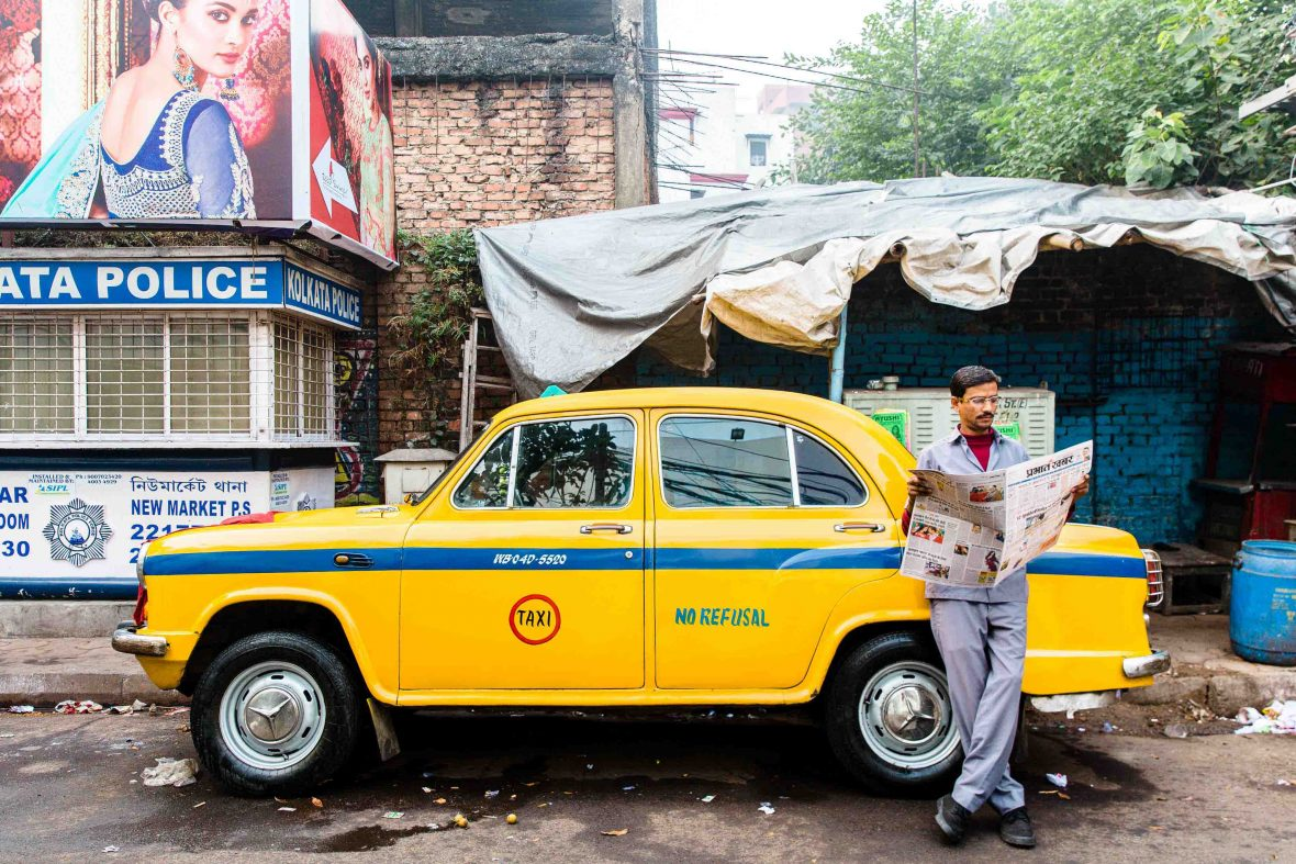 A man reads a newspaper in front of a classic yellow Ambassador taxi cab in Kolkata, West Bengal, India.