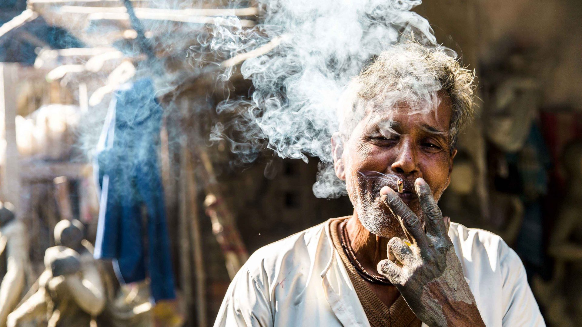 An idol maker takes a cigarette break in the Kumarkali district of Kolkata, an area known for artisans who make Hindu god and goddess statues used at festivals across India.