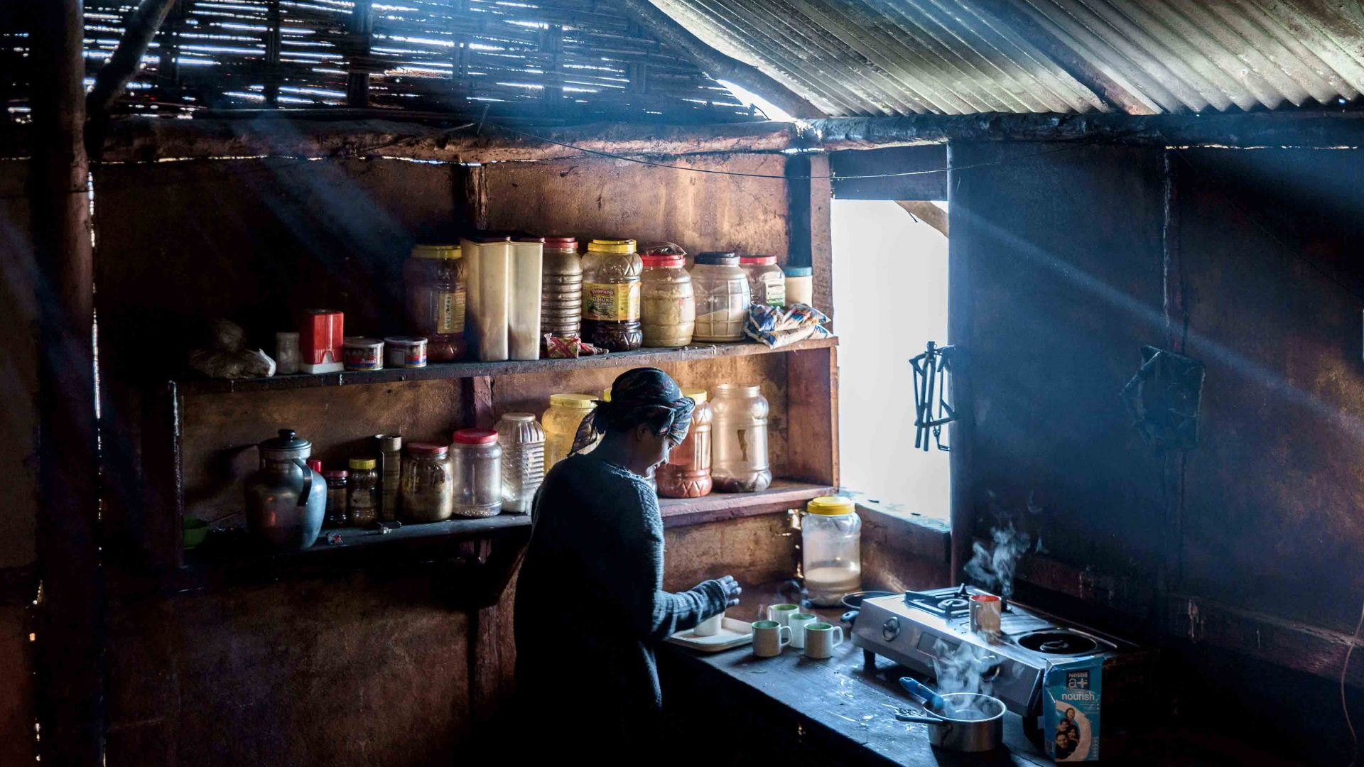 A woman makes tea in a Monpa kitchen in Arunachal Pradesh, India.