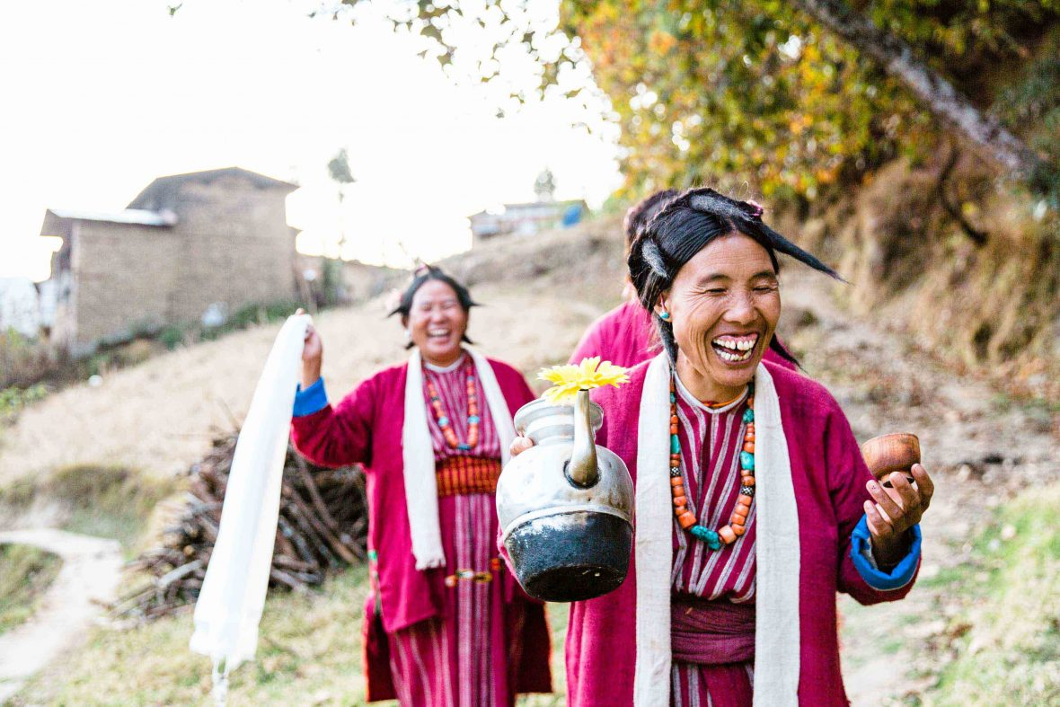 Monpa women in traditional dress carry a pot of arra, the local wine, and white khatas (ceremonial scarves) from the village of Kipti in the Tawang Valley, Arunachal Pradesh, India.