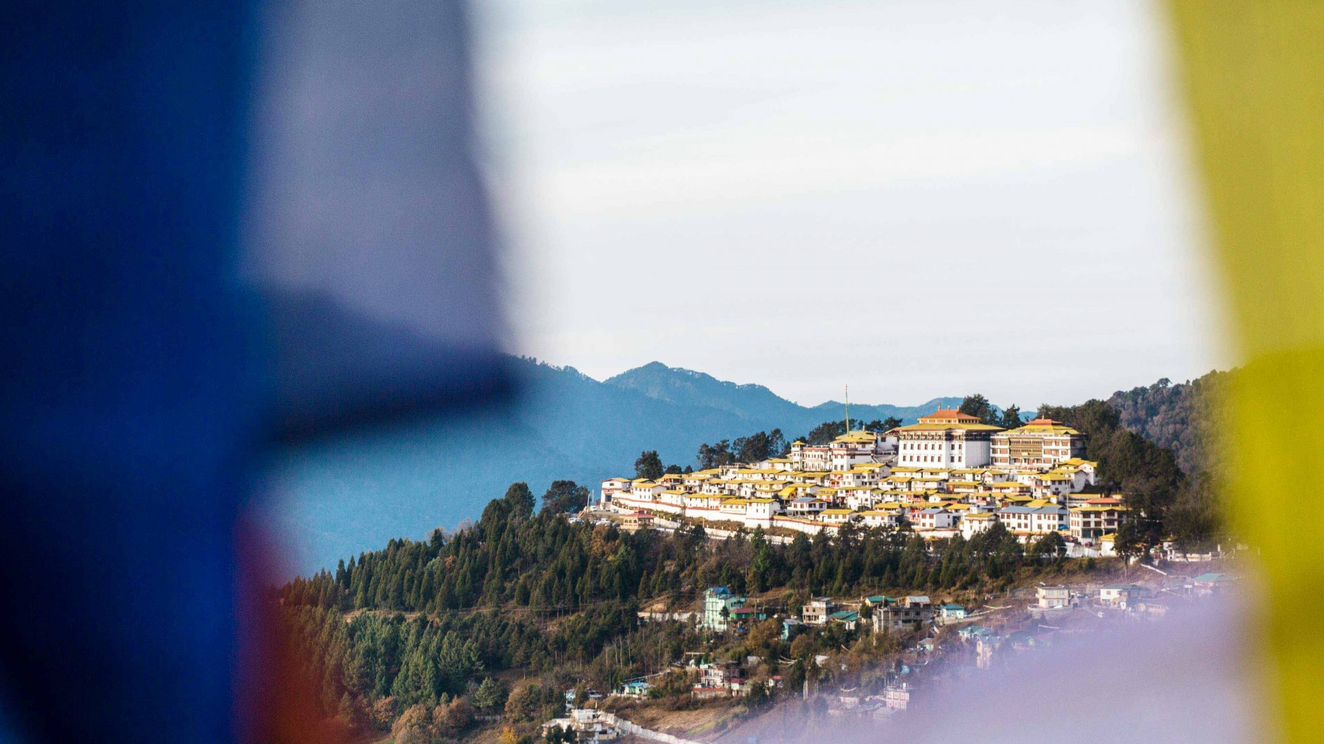 A view of the Tawang Monastery through Buddhist prayer flags in Arunachal Pradesh, India.