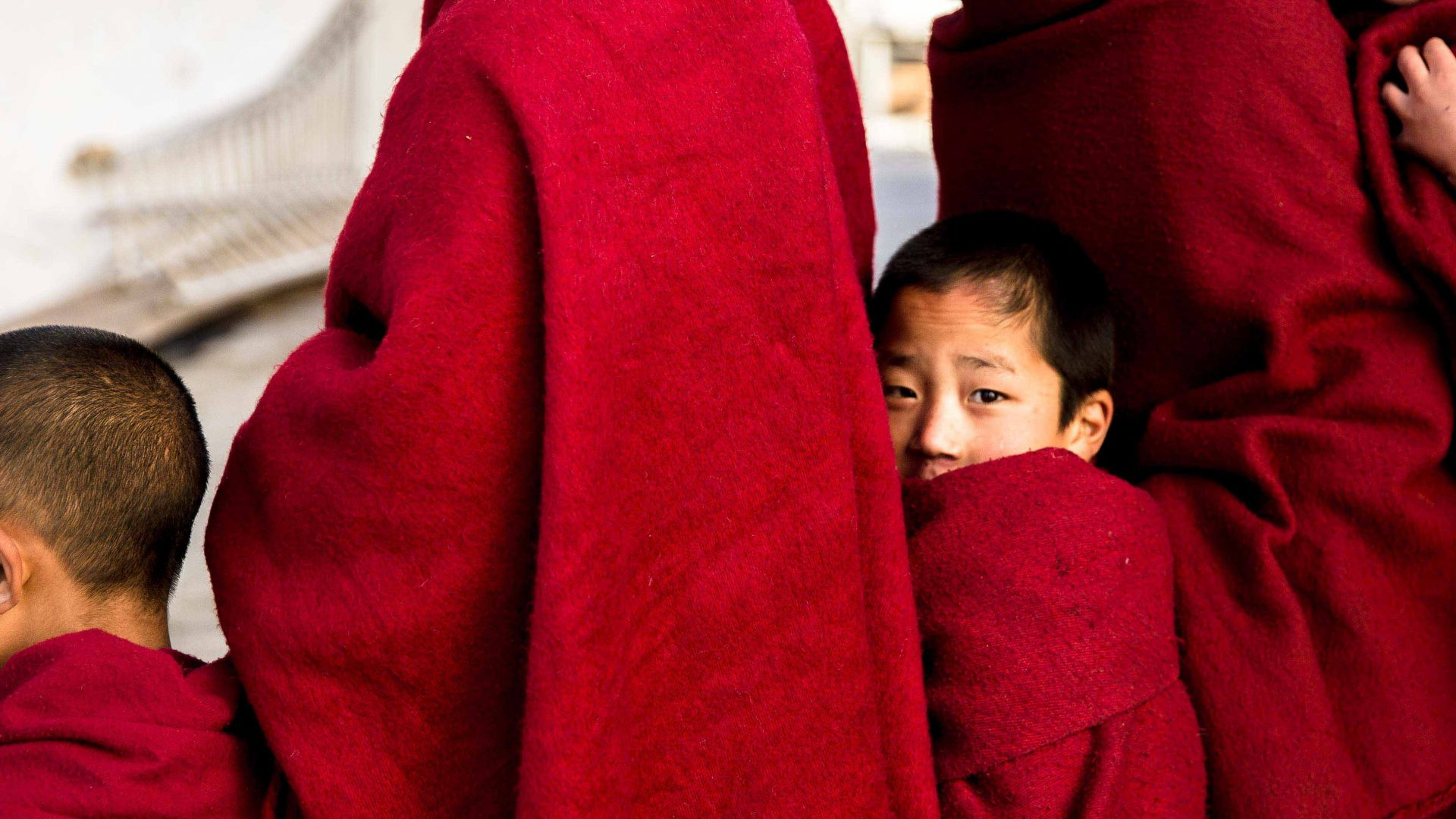A young monk peeks thorough the robes of his elders while queuing for breakfast at the Tawang Monastery, Arunachal Pradesh, India.